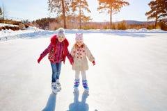 Lycklig barnskridskoåkning på en isisbana utomhus sport och en sund livsstil Roliga ungar, är de systrar och flickvänner royaltyfri fotografi