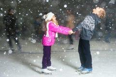 Lycklig barnskridskoåkning på isisbanan, vinternatt Arkivbild