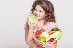 Lycklig barnstående med organiska grönsaker, liten flicka som ler, studio Royaltyfri Foto