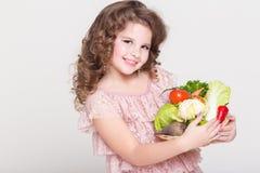 Lycklig barnstående med organiska grönsaker, liten flicka som ler, studio Royaltyfri Fotografi