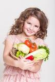 Lycklig barnstående med organiska grönsaker, liten flicka som ler, studio Arkivbilder