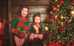 Lycklig barnsyskongruppälva, hjälpreda av jultomten med Chri royaltyfria foton