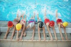 Lycklig barnungegrupp på simbassänggrupp som lär att simma Arkivbild