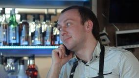 Lycklig bartender i förkläde som kallar på smartphonen på stången Royaltyfri Bild
