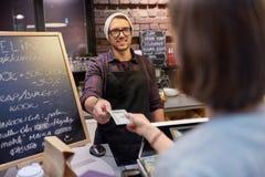 Lycklig bartender och kvinna som betalar pengar på kafét Royaltyfria Foton