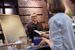 Lycklig bartender och kvinna som betalar pengar på kafét Arkivbilder
