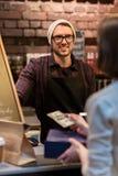Lycklig bartender och kvinna som betalar pengar på kafét Arkivbild
