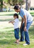 lycklig baseballfader hans son som undervisar till Arkivfoton