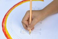lycklig begreppsfamilj Barnet drar på ett ark av papper: fader-, moder-, pojke- och flickahållhänder mot bakgrund av regnbågen arkivfoto