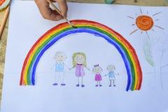 lycklig begreppsfamilj Barnet drar på ett ark av papper: fader-, moder-, pojke- och flickahållhänder mot bakgrund av regnbågen oc royaltyfri fotografi