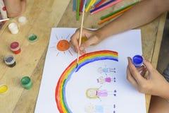 lycklig begreppsfamilj Barnet drar på ett ark av papper: fader-, moder-, pojke- och flickahållhänder mot bakgrund av regnbågen oc royaltyfri foto