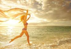 Lycklig bekymmerslös kvinnaspring i solnedgången på stranden royaltyfria foton