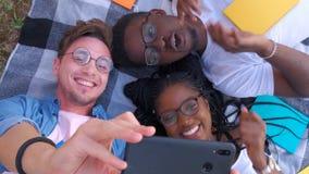 Lycklig blandras- vängrupp som tar selfie med den mobila smarta telefonen - ungt hipsterfolk som missbrukas av smartphonen på arkivfilmer