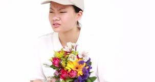 Lycklig blommaleveranskvinna som söker efter häftet lager videofilmer