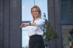 Lycklig blond affärskvinna som kontrollerar tid med klockan på hennes hand mot av kontorsbyggnad arkivfoton