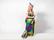 Lycklig blond barnflicka i färgrik klänning för hippie mot den vita väggen Arkivfoto