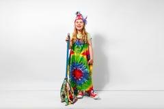Lycklig blond barnflicka i färgrik klänning för hippie mot den vita väggen Royaltyfri Foto