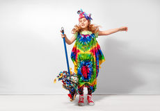 Lycklig blond barnflicka i färgrik klänning för hippie mot den vita väggen Arkivbilder