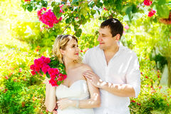 Lycklig blond brud och brudgum som har gyckel på en tropisk trädgård wed arkivfoton