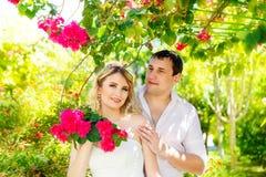 Lycklig blond brud och brudgum som har gyckel på en tropisk trädgård wed arkivbild