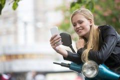 Lycklig blond flicka på sparkcykeln genom att använda mobiltelefonen Royaltyfria Bilder