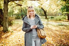 Lycklig blond kvinna i en h?stlig skog eller att parkera att smsa med hennes mobiltelefon Kommunikations-, teknologi- och det fri royaltyfria bilder