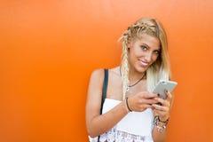Lycklig blond kvinna i en orange bakgrundsvägg genom att använda en mobil ph Royaltyfria Bilder