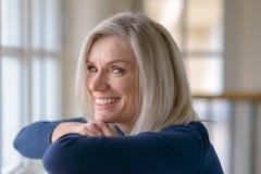 Lycklig blond kvinna med ett livligt vänligt leende royaltyfri fotografi