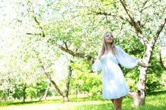 Lycklig blond kvinna på en bakgrund av att blomma vårträdgården med hennes händer som lyfts till himlen royaltyfria bilder