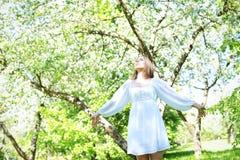 Lycklig blond kvinna på en bakgrund av att blomma vårträdgården med hennes händer som lyfts till himlen arkivfoton