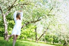 Lycklig blond kvinna på en bakgrund av att blomma vårträdgården med hennes händer som lyfts till himlen arkivbilder