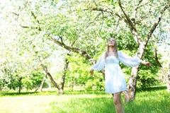 Lycklig blond kvinna på en bakgrund av att blomma vårträdgården med hennes händer som lyfts till himlen royaltyfri foto