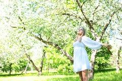 Lycklig blond kvinna på en bakgrund av att blomma vårträdgården med hennes händer som lyfts till himlen arkivbild