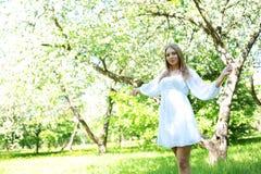 Lycklig blond kvinna på en bakgrund av att blomma vårträdgården med hennes händer som lyfts till himlen royaltyfri fotografi