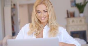 Lycklig blond kvinna som använder hennes bärbar datordator Arkivfoto