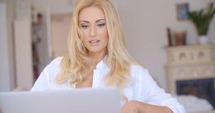 Lycklig blond kvinna som använder hennes bärbar datordator Royaltyfria Foton
