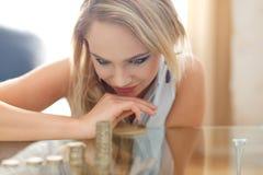 Lycklig blond kvinna som räknar myntkolonner Royaltyfria Bilder