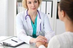 Lycklig blond kvinnlig doktor som ser patienten, medan tala till henne och att uppmuntra Medicin, sjukvård och hel arkivfoto