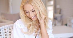 Lycklig blond kvinnlig som kallar på telefonen som ser lämnad Royaltyfri Fotografi