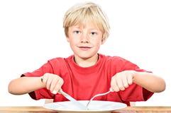 Lycklig blond pojke som äter en ärta arkivbilder