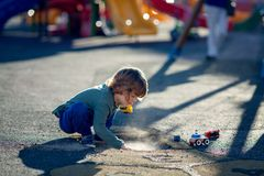 Lycklig blond pojke som spelar i parkera med smuts från ett krukahål Royaltyfri Fotografi