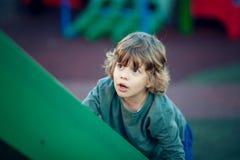 Lycklig blond pojke som spelar i parkera på den gröna glidaren Arkivfoton
