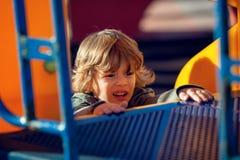 Lycklig blond pojke som spelar i parkera på den orange glidaren Royaltyfri Fotografi