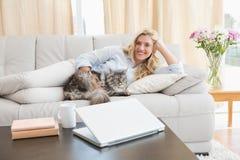 Lycklig blondin med den älsklings- katten på soffan fotografering för bildbyråer