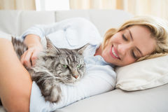 Lycklig blondin med den älsklings- katten på soffan Royaltyfria Bilder