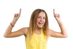Lycklig blondin med lockigt hår, tonårig flicka som pekar upp hennes pekfinger och att indikera kopieringsutrymme på den vita tom royaltyfri foto