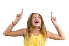 Lycklig blondin med lockigt hår, tonårig flicka som pekar upp hennes pekfinger och att indikera kopieringsutrymme på den vita tom arkivbilder