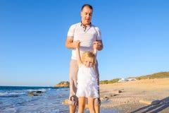 Lycklig blondy barnflicka med hennes faderinnehavhänder och hagyckel som går på stranden Familjsemester, loppbegrepp brigham fotografering för bildbyråer