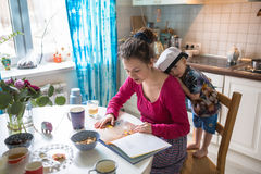 Lycklig bok för kök för för familjmamma och son hemmastadd läst tillsammans Arkivbild
