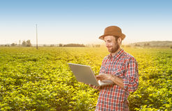 Lycklig bonde med bärbar datordatoren framme av fältet Royaltyfri Foto